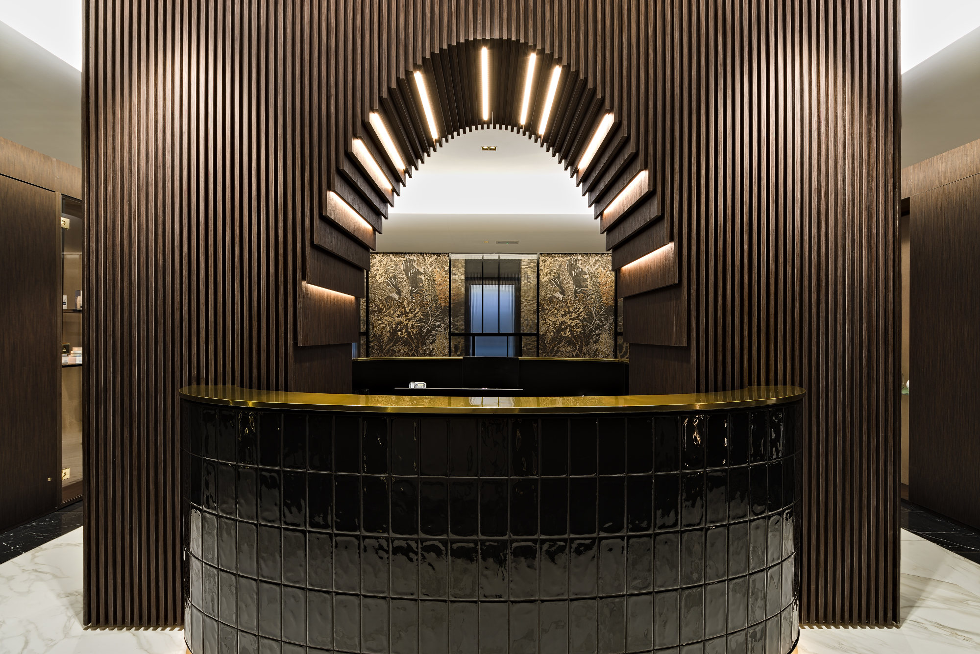 Reception desk with black ceramic tiles, wood arc and brass finishes